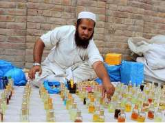 MULTAN: Vendor busy in arranging and displaying traditional perfume (attar) at his roadside setup.