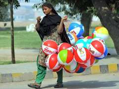 MULTAN: A lady street vendor selling balloons while shuttling on the road.