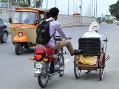 MULTAN: A motorcyclist pushing wheelchair with his foot to help a disable person to reach his destination at Boson Road.