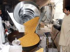 LAHORE: Labourers mixing spices in pulse at their work place.