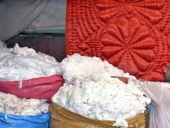 LAHORE: A labourer displaying and arranging cotton to attract the customers outside his shop.