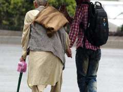 RAWALPINDI: A youngster helping an elderly person to protect from rain under the cover of umbrella.