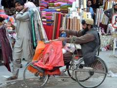QUETTA: A handicap person on the way on wheelchair to sell shopping bags in market.