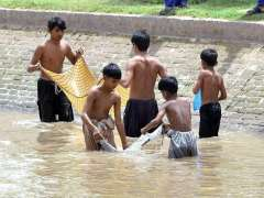 MULTAN: Gypsy children fishing in traditional way in a local canal.