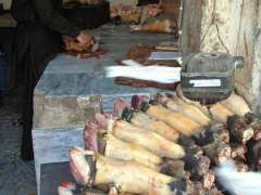 RAWALPINDI: A vendor busy in cleaning animal feet for sell at his selling point.