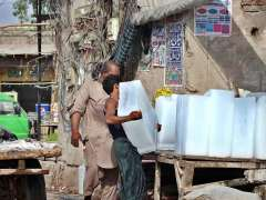 MULTAN: Labourer busy in unloading ice block from donkey cart at roadside setup.