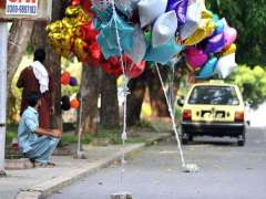 ISLAMABAD: A street vendor displaying different shaped of air filled balloons to attract customers.