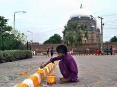 MULTAN: A worker busy in painting the road divider in front of Hazrat Shah Rukn-e-Alam Shrine.