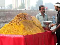 FAISALABAD: A street vendor displaying traditional sweet items to attract the customers.