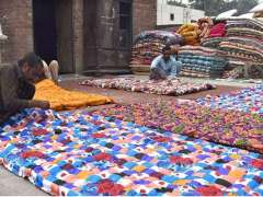 LAHORE: Labourers stitching quilts at their workplace.