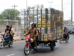 MULTAN: A person driving overloaded motorcycle rickshaw with empty oil boxes, may cause any untoward incident.