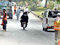 ISLAMABAD: Workers busy in marking center line on road in Federal Capital.