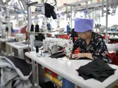 TONGXIN (China'): A worker makes clothes at a factory in a poverty alleviation industrial park in Tongidn County, Wuzhong City of northwest China's Ningxia Hui Autonomous Region. The industrial park aiming to alleviate poverty in the region was set up in 2014, which has provided more than 1,300 job opprtunities so far.