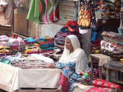 KARACHI: An old woman selling cloth at Lyari to earn livelihoods for her family.