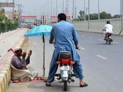 MULTAN: Beggar asking for some mercy from motorcyclist at Boson Road.