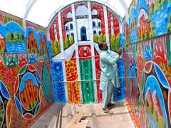 MULTAN: A painter painting a delivery truck parked at his workplace.
