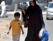 راولپنڈی: خاتون دھوپ کی شدت سے بچنے کے لیے چھتری تانے جا رہی ہے۔