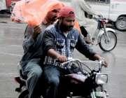 را ولپنڈی: موٹر سائیکل سوار بارش سے بچنے کے لیے پلاسٹک شیٹ سر پر رکھے ..