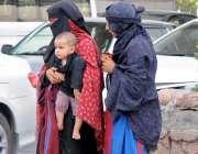 راولپنڈی: سخت دھوپ میں خانہ بدوش خواتین اپن بچوں کے ہمراہ رمی روڈ پر ..