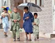 اسلام آباد: بچوں نے بارش سے بچنے کے لیے چھتری تان رکھی ہے۔