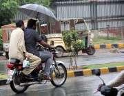 سرگودھا: موٹر سائیکل سوار بارش سے بچنے کے لیے چھتری تانے جا رہے ہیں۔