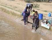 لاہور : خانہ بدوش خواتین نہر کنارے کپڑے دھورہی ہیں۔