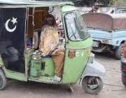 لاہور: ایک بزرگ راہگیر خاتون پریس کلب کے باہر رکشے میں بیٹھے کر آرام ..