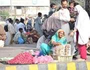 لاہور: داتا دربار حاضری کے لیے آنے والی ایک فیملی تبرک خرید رہی ہے۔