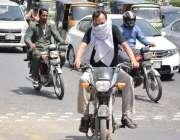 لاہور: ایک موٹر سائیکل سوار گرمی کی شدت سے بچنے کے لیے منہ کو کپڑے سے ..