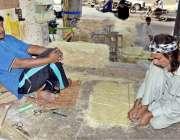 لاہور: ایک کاریگر ائیر کولر کی خسیں تیار کرنے میں مصروف ہے۔