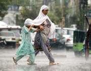 راولپنڈی: بارش کے دوران ایک خاتون اپنی بیٹی کے ساتھ  سڑک عبور کرتے ہوئے