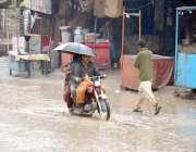 ڈیرہ اللہ یار: موٹر سائیکل سوار بارش سے بچنے کے لیے چھتری تانے جارہے ..