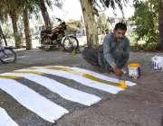 فیصل آباد: مزدور سپیڈ بریکر کو رنگ کرنے میں مصروف ہے۔