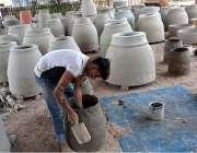 فیصل آباد: محنت کش روایتی انداز سے تندور بنانے میں مصروف ہے۔