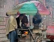 را ولپنڈی: بارش کے دوران شہری ایک ریڑھی بان سے مکئی کے گرم دانے خرید ..