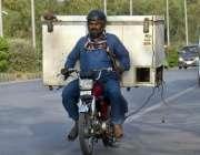راولپنڈی:ایک شخص موٹر سائیکل پر فرج رکھے ائیر پورٹ روڈ سے گزر رہا ہے۔
