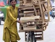 راولپنڈی: محنت کش سائیکل پر سٹول رکھے فروخت کے لیے پھیری لگا رہا ہے۔