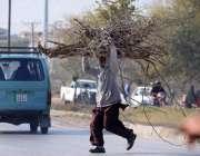 راولپنڈی: نوجوان خشک لکڑیاں اٹھائے سڑک کراس کررہا ہے۔