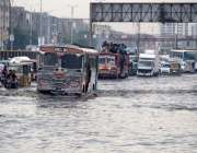 کراچی: شہر میں موسلا دھار بارش کے بعد ناگین چورنگی پر جمع پانی سے گزرتی ..