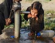 لاہور: ایک کمسن بچی ہینڈ پمپ سے پانی پی رہی ہے۔