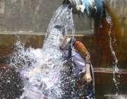 ملتان: خاتون گرمی کی شدت کم کرنے کے لیے ٹیوب ویل کے پانی سے نہا رہی ہے۔