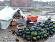 فیصل آباد: محنت کش نے تربوز فروخت کے لیے سجا رکھے ہیں جبکہ بارش سے بچنے ..