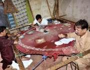 فیصل آباد: مدینہ ٹاؤن میں مزدور اپنے کام کی جگہ پر کڑھائی کے کاموں میں ..