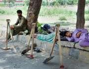 اسلام آباد: مزدور کام نہ ہونے کے باعث درختوں کے سائے تلے آرام کر رہے ..