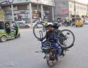 لاہور: ایک موٹر سائیکل سوار شہری اپنے بیٹے کے لیے سائیکل خرید کر لیجا ..
