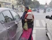 لاہور: ایک خاتون اپنے بچے کو اٹھائے ٹریفک سگنل پر بھیک مانگ رہی ہے۔