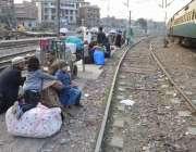لاہور: ریلوے اسٹیشن پر مسافر ٹرین کے انتظار میں بیٹھے ہیں۔