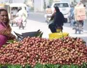 لاہور: ایک محنت کش خاتون لیچیاں فروخت کرنے کے لیے گاہکوں کا انتظار کررہی ..