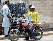 ملتان: موٹر سائیکل سوار شہری سڑک کنارے لگے سٹال سے عینک خرید رہا ہے۔