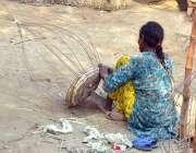 ملتان:خاتون اپنے کام کی جگہ پر خشک درخت کی شاخوں والی روایتی ٹوکری بنا ..